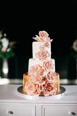 gold and white wedding cake with cascading blush roses