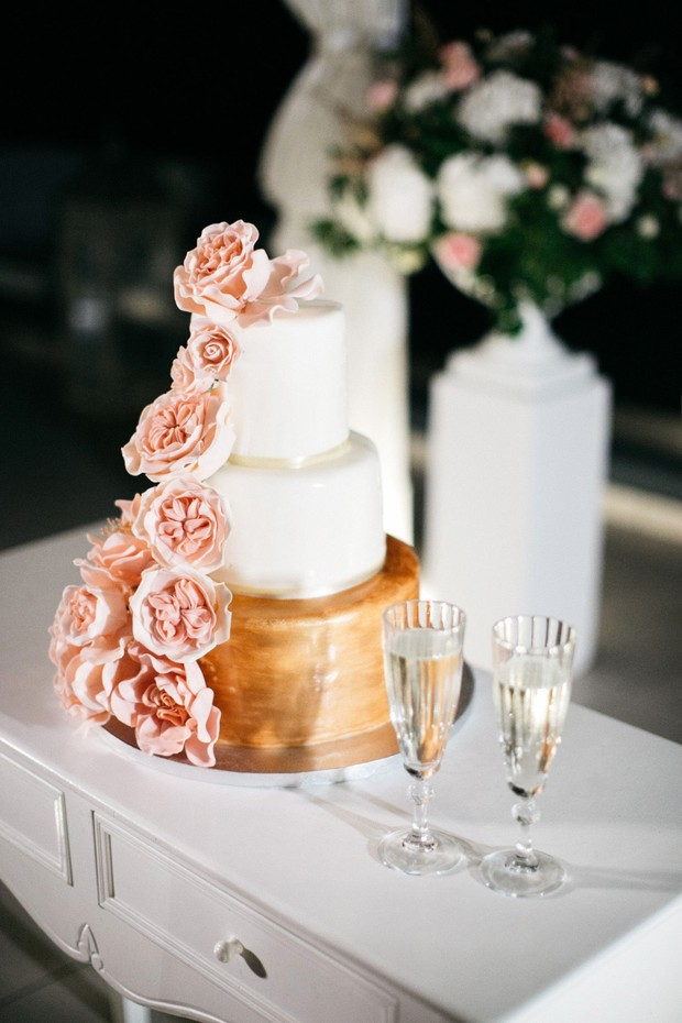 gold and white wedding cake with blush roses