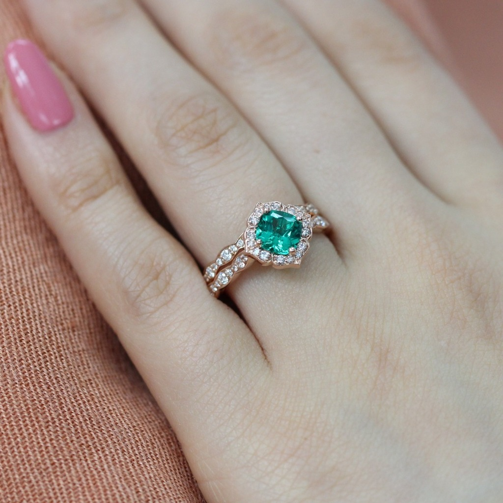 Intricate yet unique emerald bridal ring set features a vintage floral engagement ring with a 6x6mm cushion cut conflict free cultured
