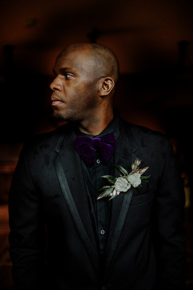 groom in all black and purple velvet bow tie