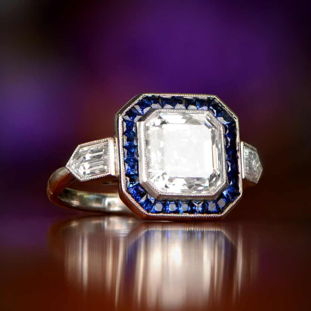 A beautiful 3-carat Asscher cut diamond, encircled by sapphire, and flanked by Bullet-cut diamonds. Curated by Estate Diamond Jewelry