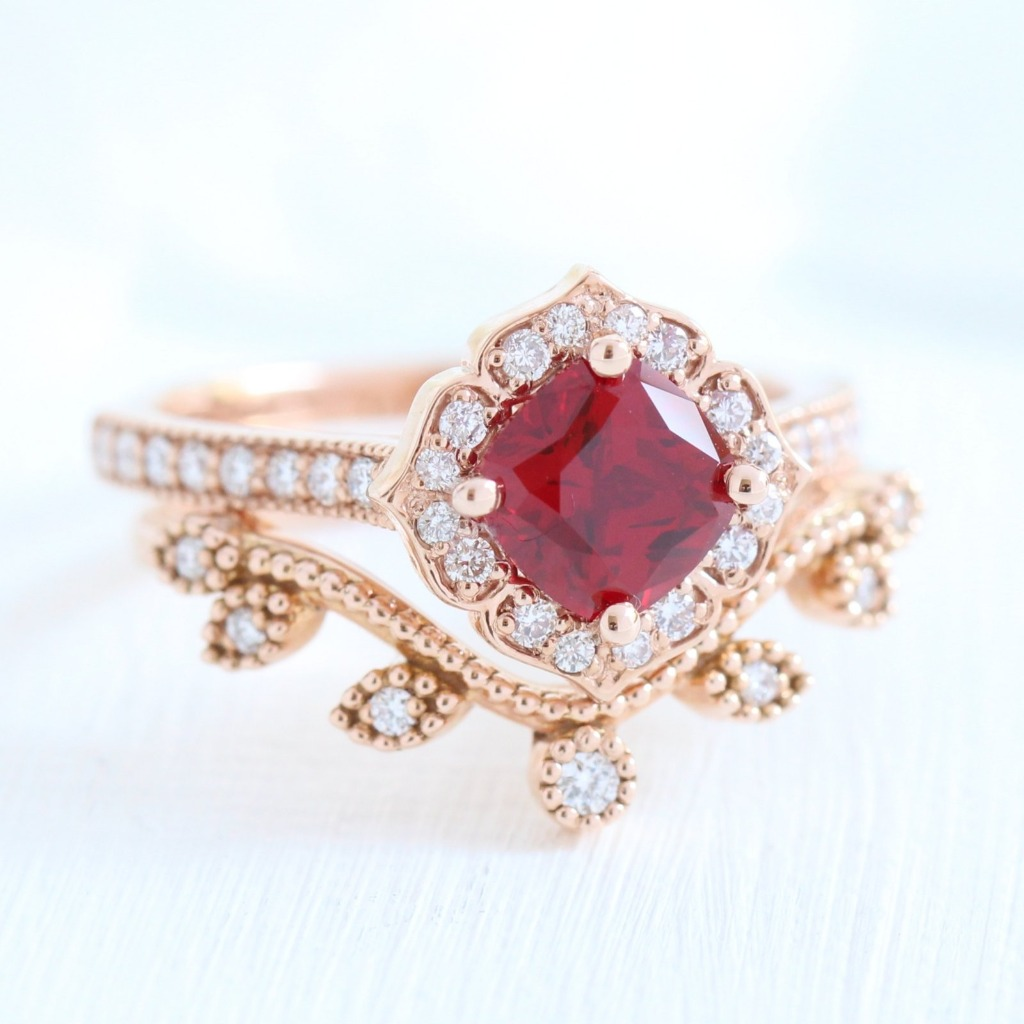 Breathtaking vintage inspired ruby bridal set features a cushion cut ruby engagement ring set in rose gold floral diamond ring setting