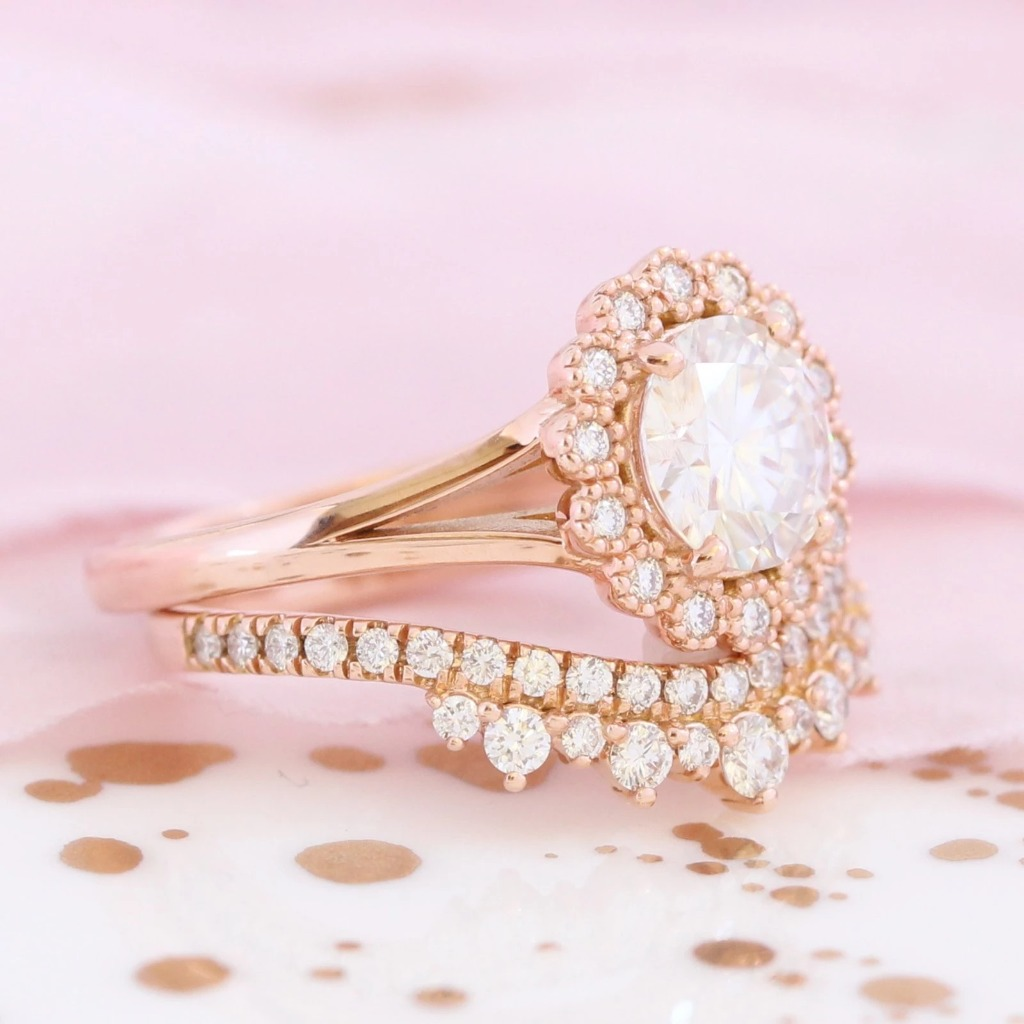 Artfully sculpted bridal ring set of a round cut moissanite engagement ring in 14k rose gold vintage halo diamond ring setting and