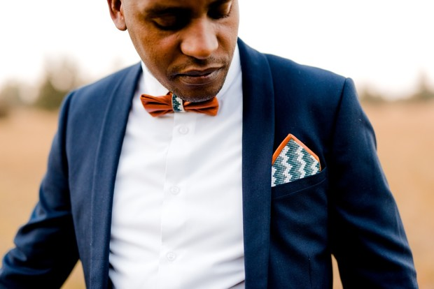 groom with beaded leather pocket square and bow tie