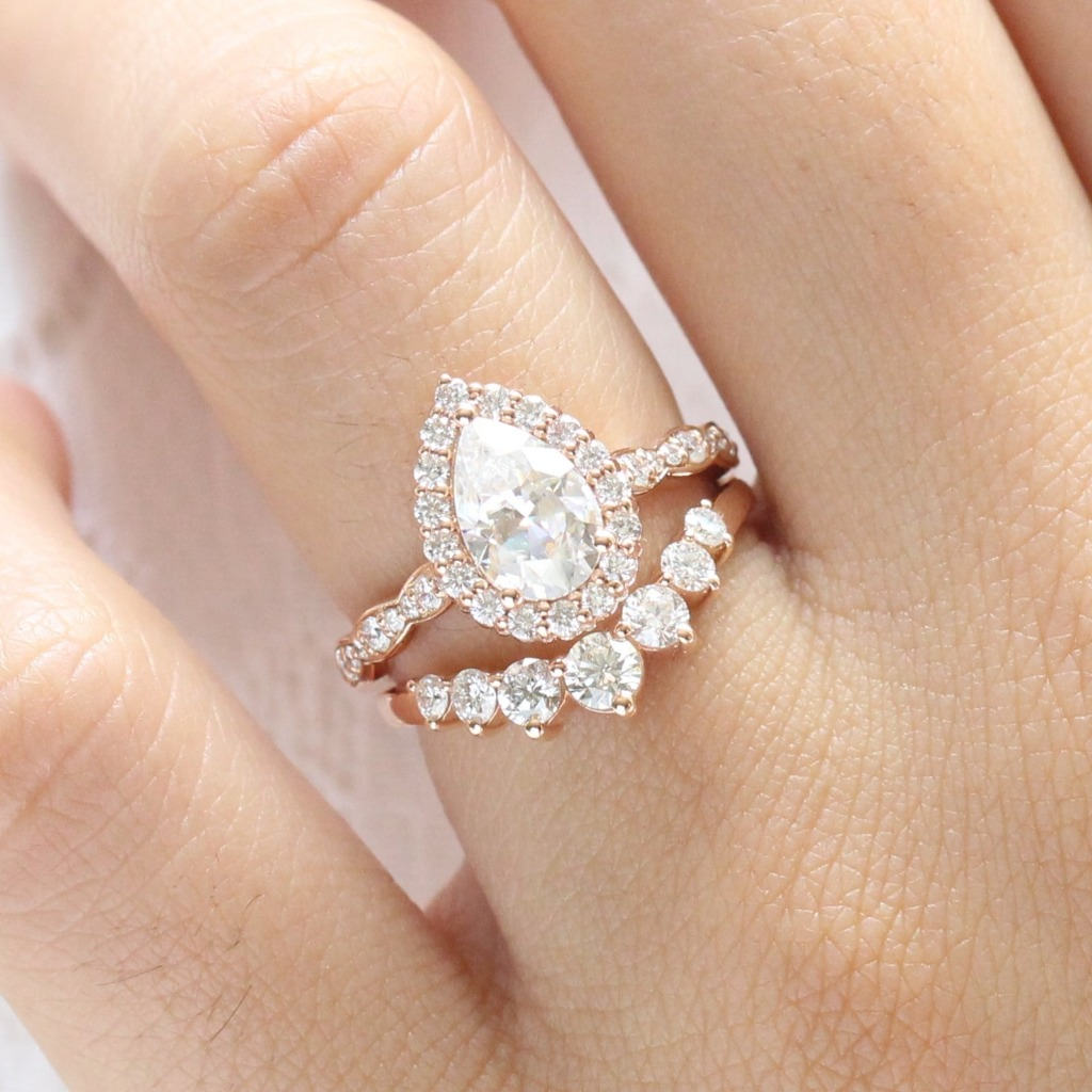 Breathtakingly gorgeous pear moissanite bridal set features a pear moissanite engagement ring in rose gold luna halo diamond scalloped