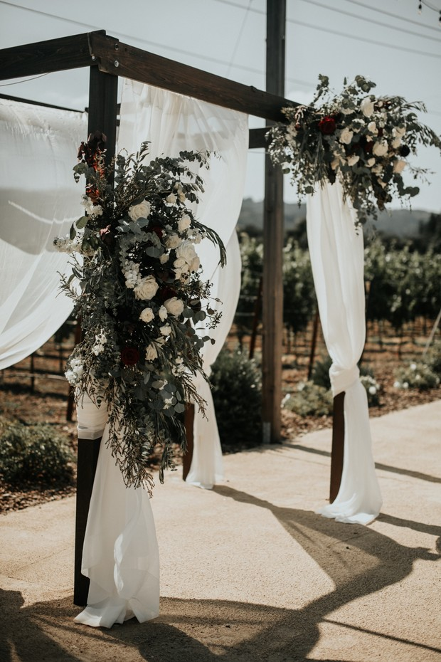 wedding arch draped in fabric and florals