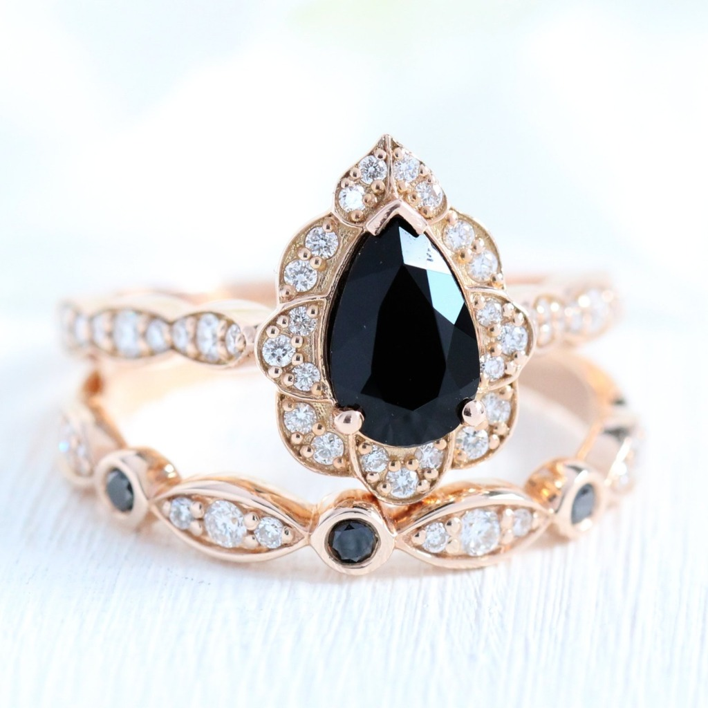 Feminine yet unique bridal set showcases a black spinel engagement ring in rose gold vintage floral diamond ring setting. To create