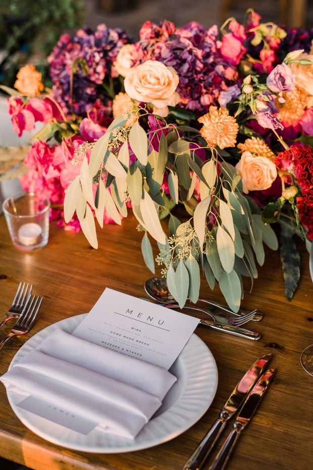 simple and chic wedding place setting with brightly colored floral centerpiece