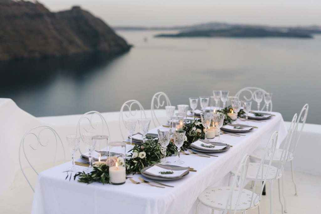 Table setting with grey and gold details, a flower table runner and the amazing santorini background.
