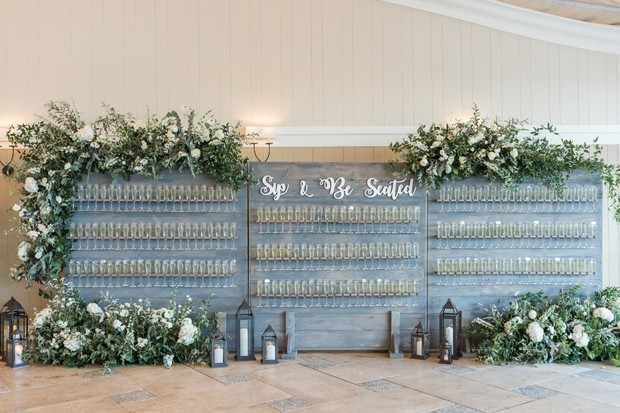sip and be seated wedding seating chart champagne wall