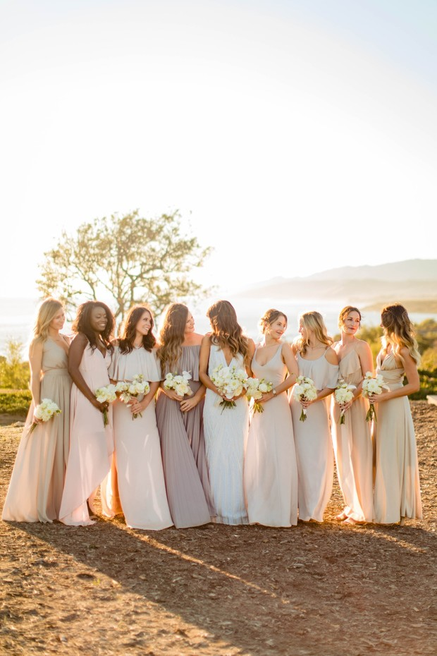 bridesmaids in muted pink and champagne dresses at sunset
