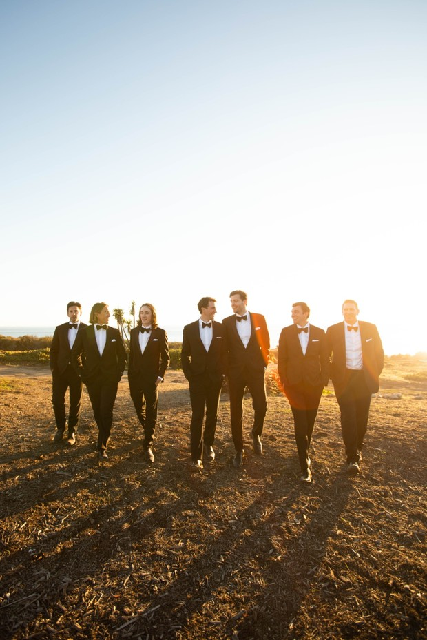 groom and his men in tuxedos at sunset