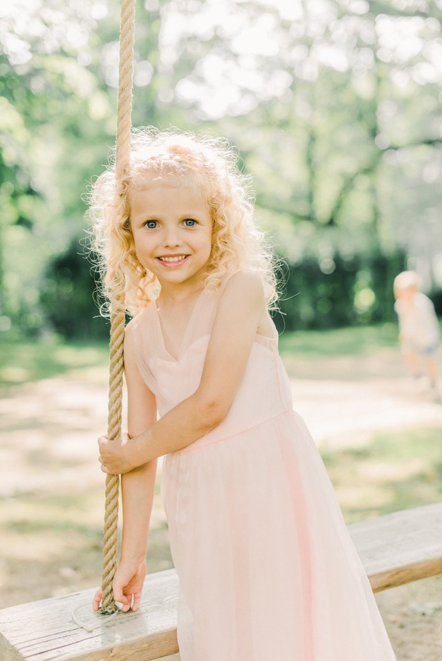 sweet little flower girl in blush dress and curly hair