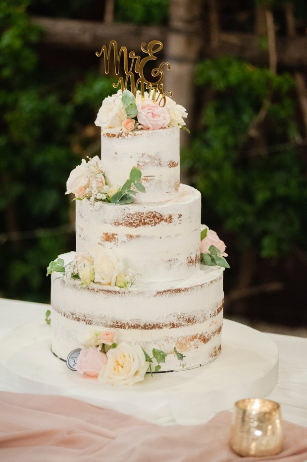 nearly naked wedding cake with blush and white flower topper