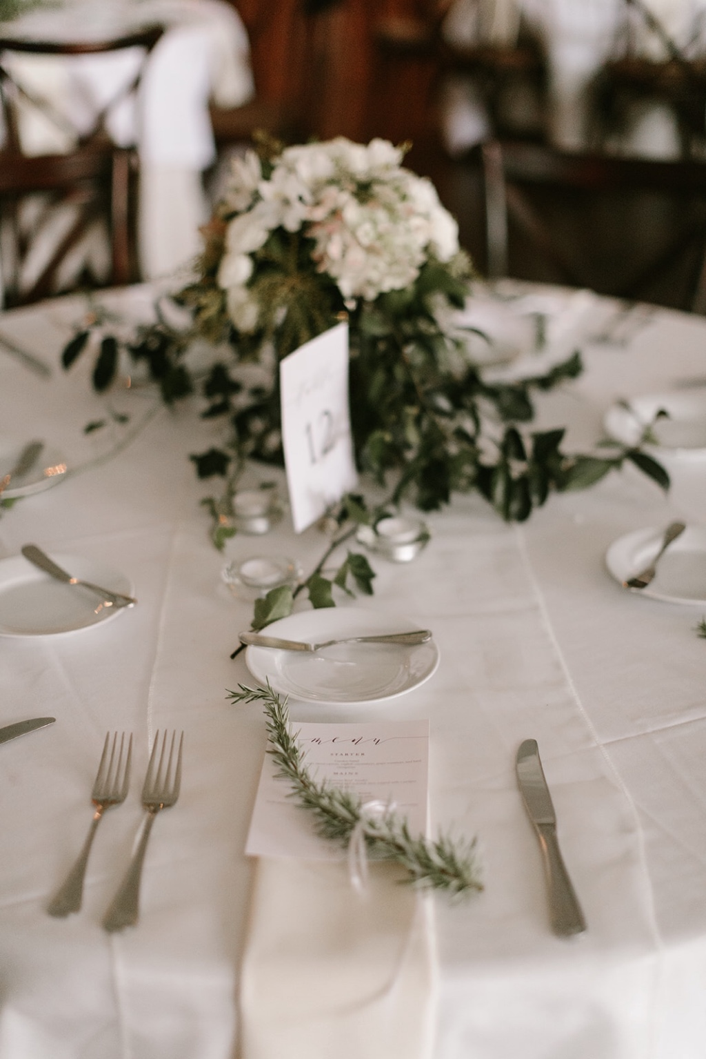 Simple elegance is sometimes the most impactful. At this winery wedding, the bride wanted all-white florals and greens, and each place