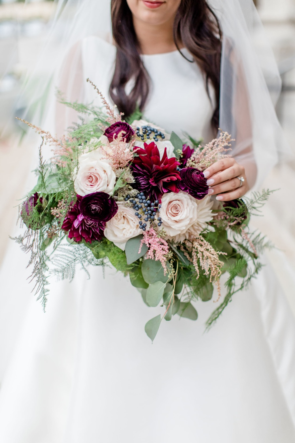 Lush blooms ranging from blush to deep burgundy are featured in this bridal bouquet with astilbe and viburnum berries to add delightful