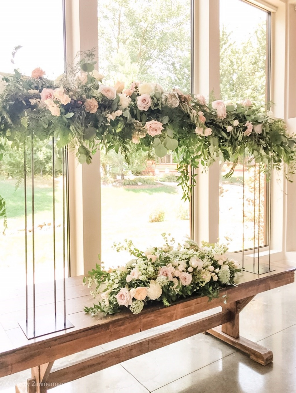 This lush tabletop pergola and floral spray were created as a beautiful backdrop for the wedding ceremony. It also was moved to the