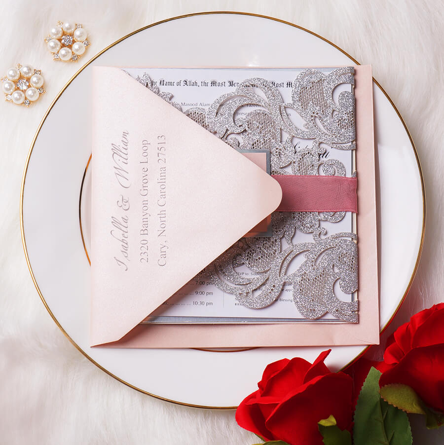 This glittering invite features soft pink ribbon and monogrammed tag. The lining of the cardstock and tag is made of mirror, luxurious