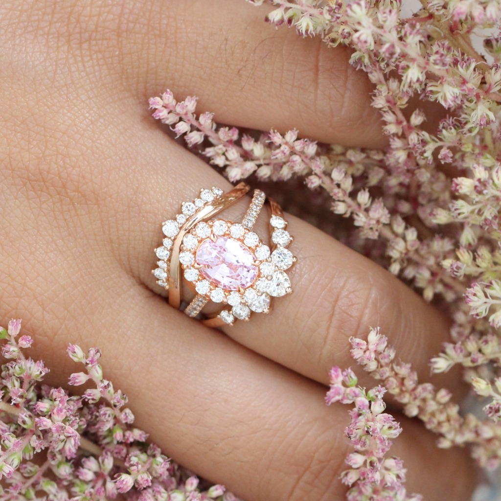 Isn't it just mesmerizing? This breathtakingly graceful bridal set features an One Of A Kind oval cut natural champagne pink sapphire