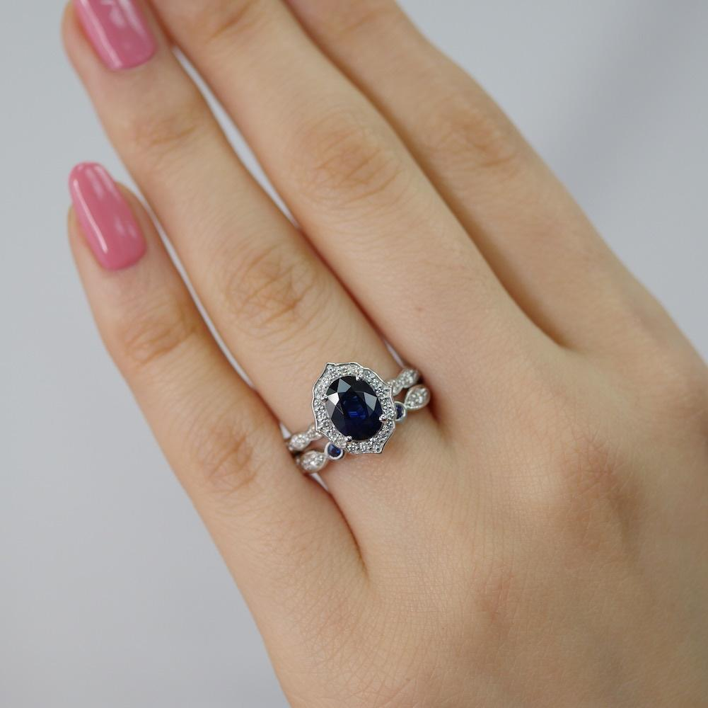 This exquisite and stunning vintage inspired sapphire bridal ring set showcases a sapphire engagement ring set in 14k white gold floral