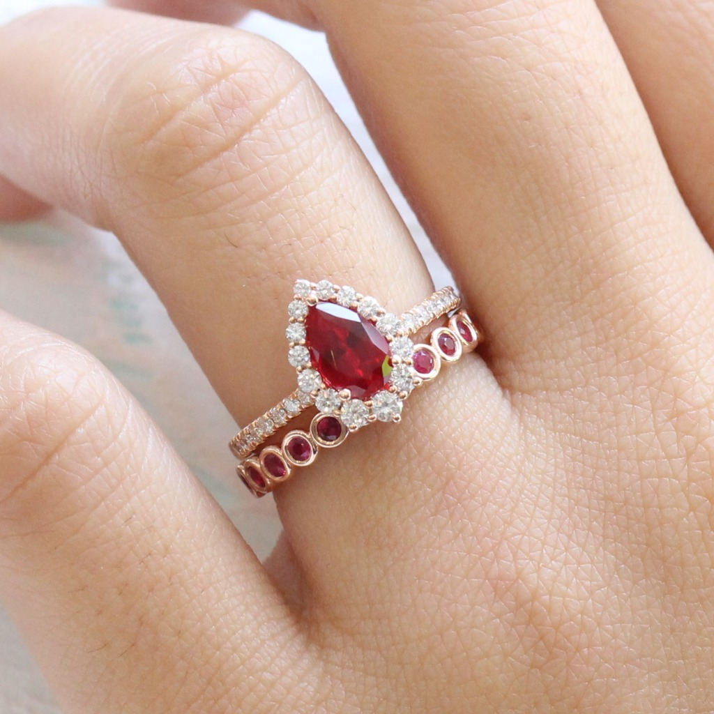 Elegantly crafted ruby ring bridal set features a ruby engagement ring set in 14k rose gold luna halo diamond ring setting with a 9x6mm