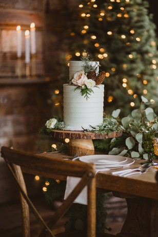 wintertime wedding cake topped with flowers and pinecones