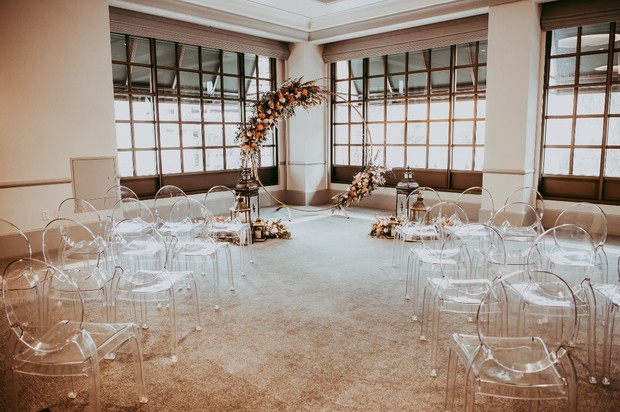 wedding ceremony with ghost chairs and giant wreath floral backdrop