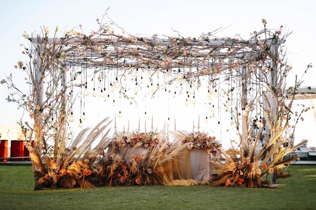 wedding sweetheart table with hanging lights and floral decor