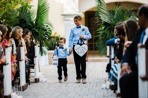 ring bearers with here comes the bride signs