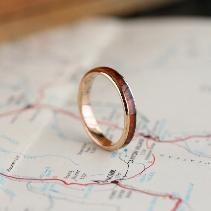 Womens rose gold wooden wedding ring. Crafted out of tungsten carbide and inlaid with natural koa wood.