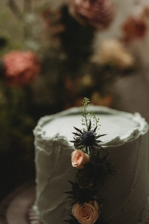 wedding cake with rose buds and thistles