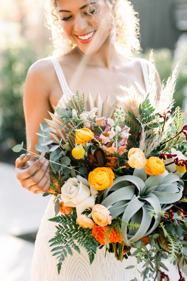 summer time wedding bouquet in yellow orange and air plants