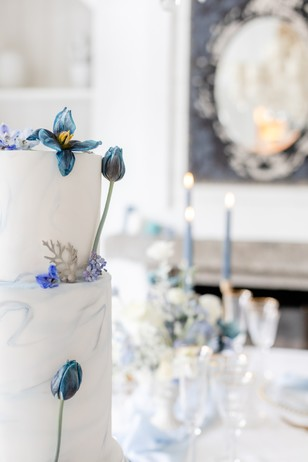 blue floral topped wedding cake