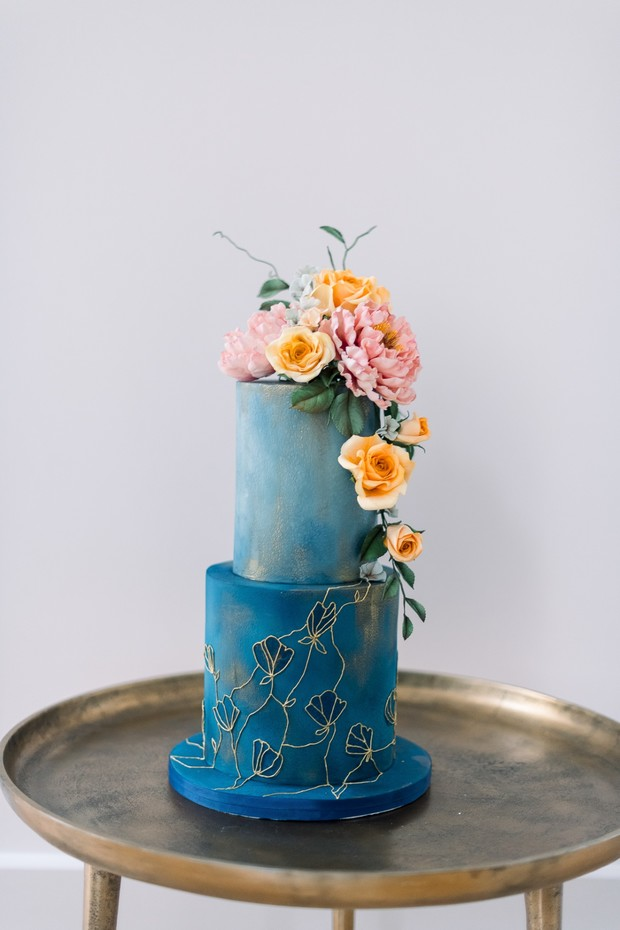 blue and gold wedding cake with florals