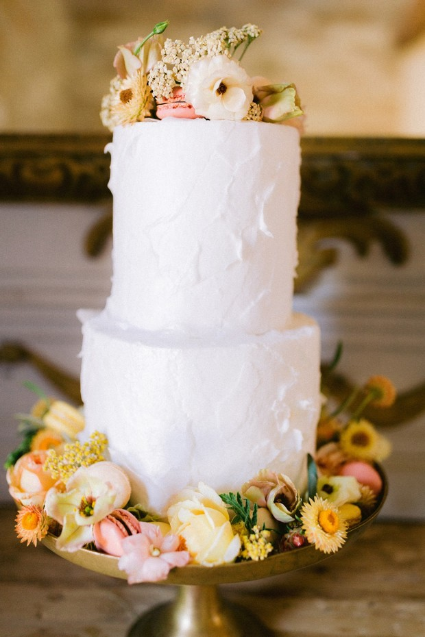 simple white wedding cake with flowers and macarons
