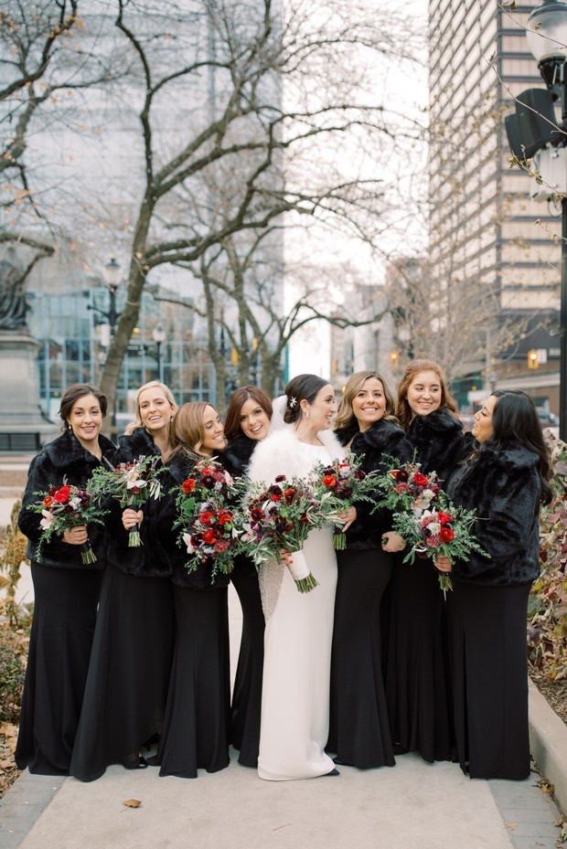 bridesmaids in black dresses with faux fur jackets