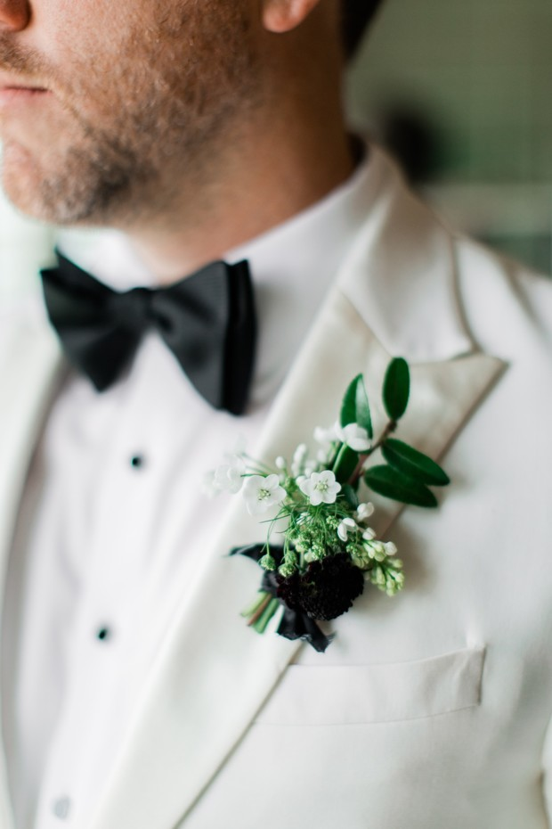 groom in white suit jacket with black and white boutonniere