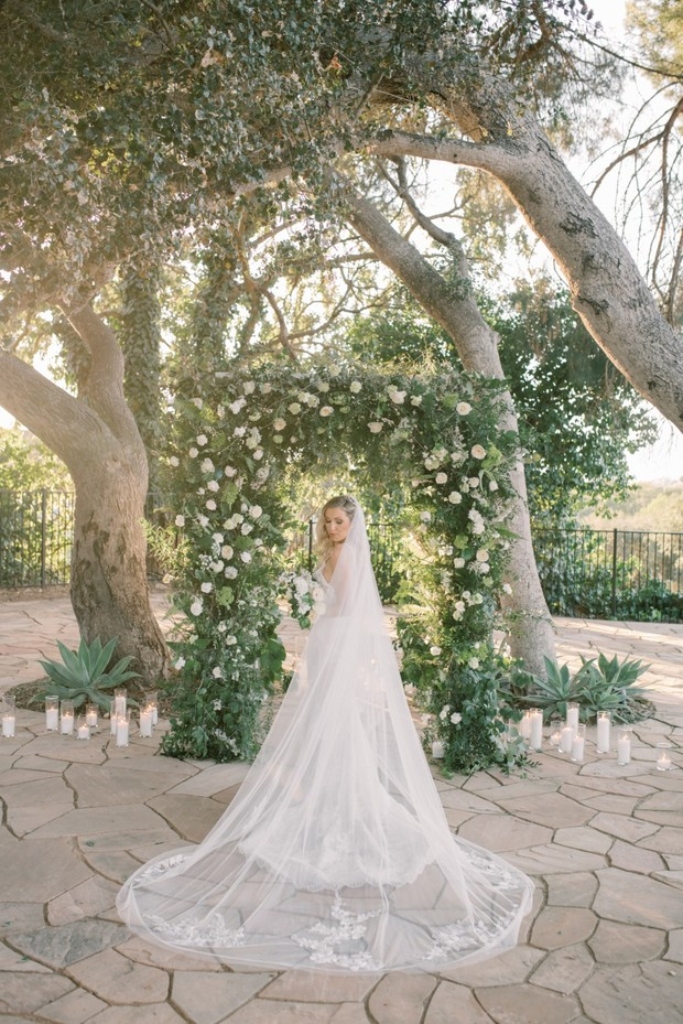 white rose arch and candle wedding ceremony backdrop