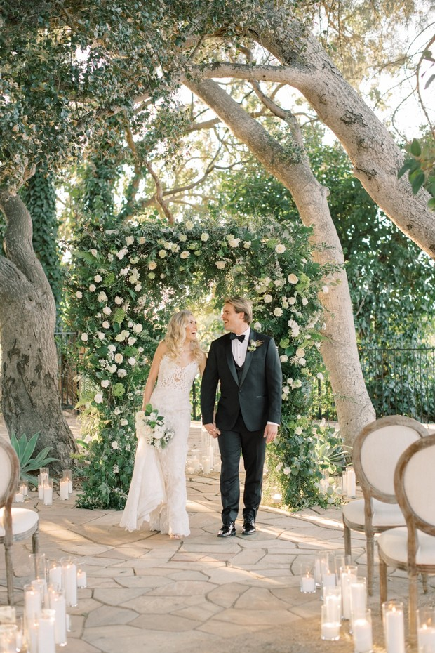 romantic candle lit wedding ceremony with white rose flower arch