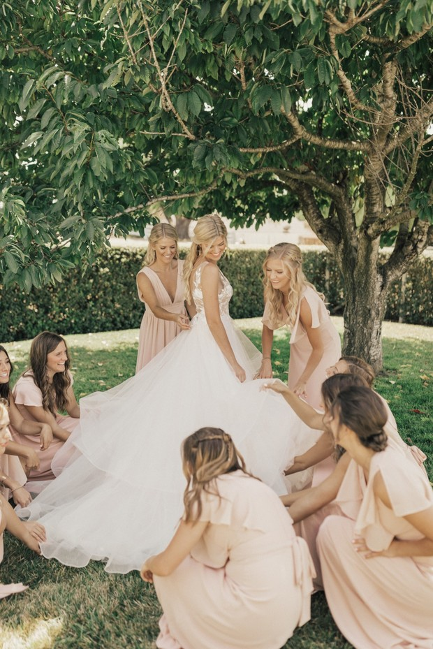 bridesmaids in blush and bride ready for her wedding