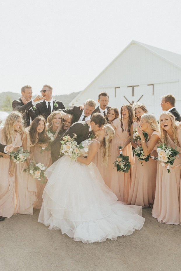 blush wedding party and newlyweds kiss