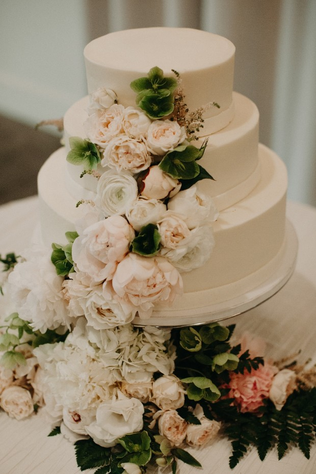 white wedding cake decorated with peonies