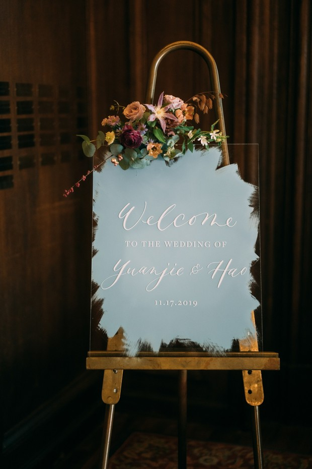 acrylic welcome wedding sign on brass sign with florals