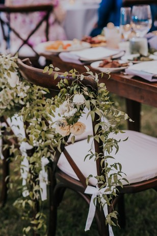 decorated wedding chairs at sweetheart table