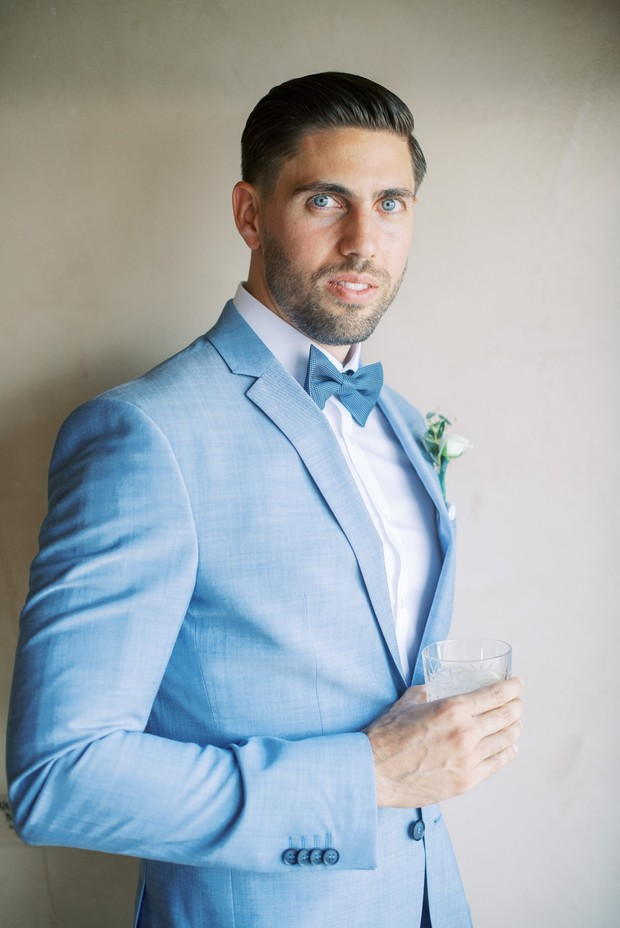 groom in light blue suit with bow tie