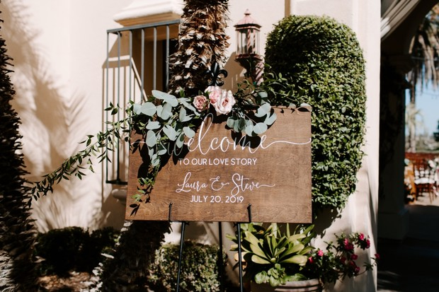 wooden welcome wedding sign with eucalyptus and roses