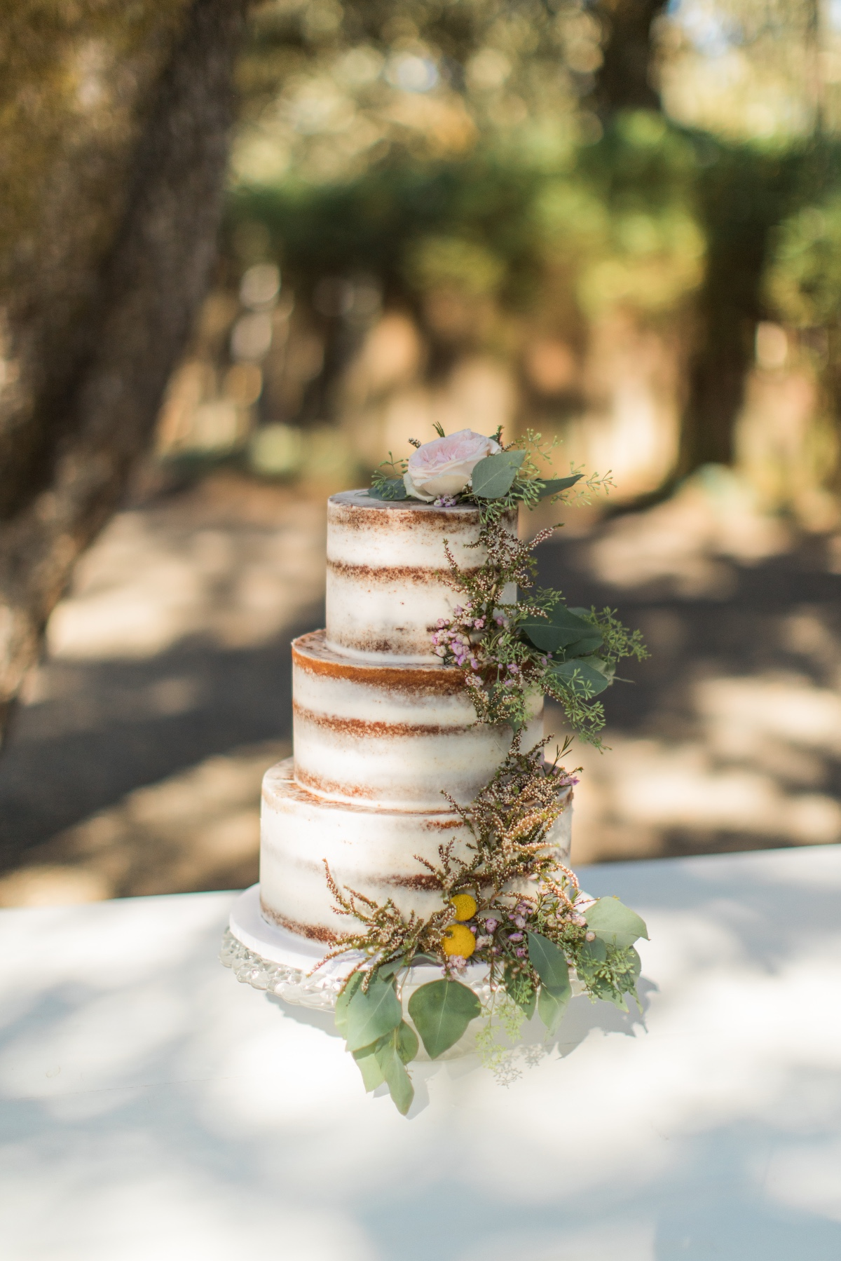 naked wedding cake adorned with greenery and florals