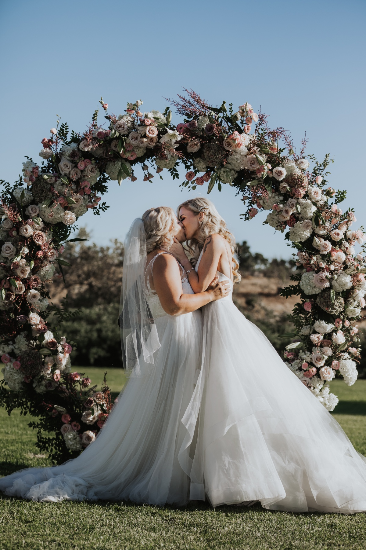 Just married wedding kiss behind floral centerpiece