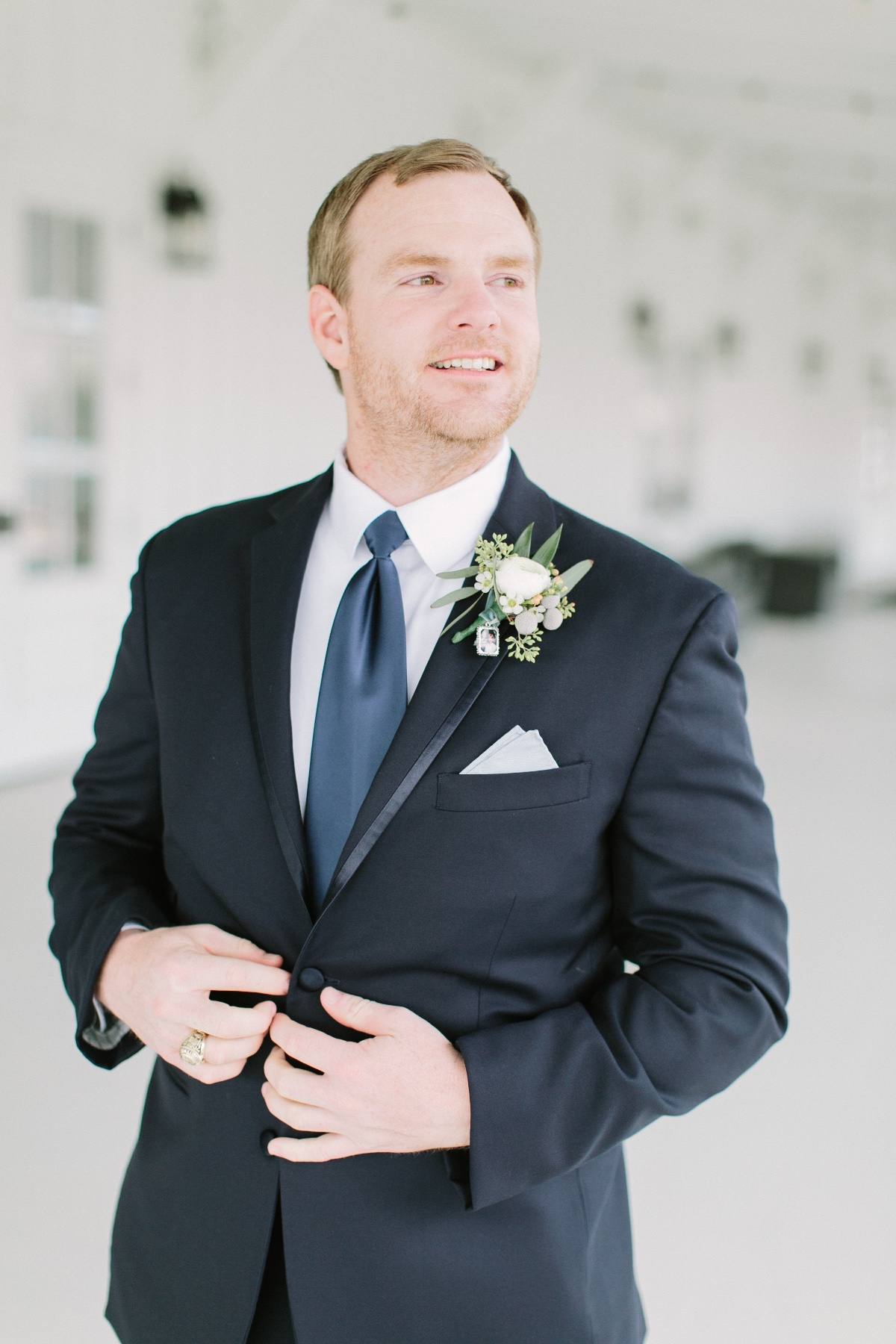 groom in black suit with blue tie and white boutonnière