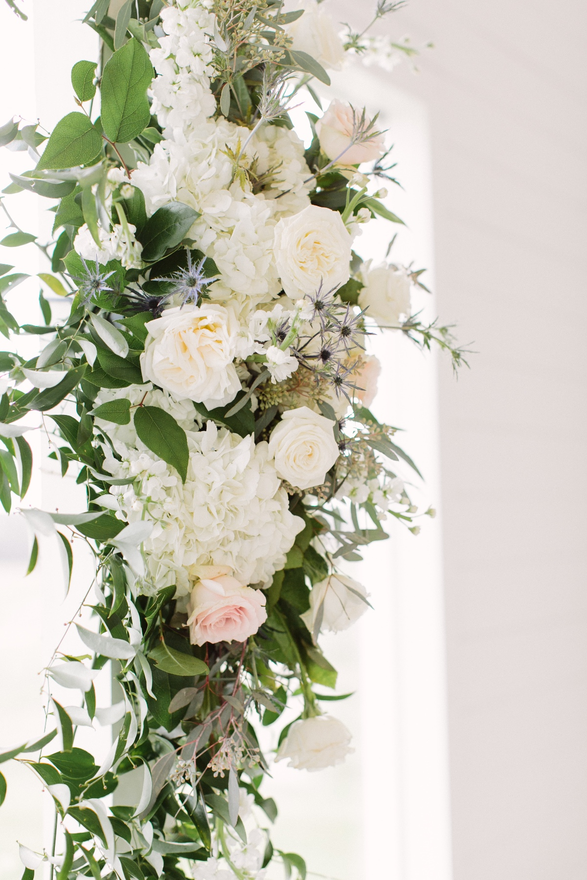 white and green florals for ceremony backdrop